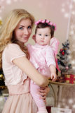 Mother hugging baby girl dressed like angel at Christmas Stock Images
