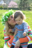 Mother hugging baby girl in spring lawn Stock Photos