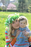 Mother hugging baby girl in spring lawn Stock Images