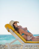 Mother hugging baby while laying on sunbed. On beach Royalty Free Stock Images