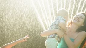 Mother Hugging Child at the Backyard on the Lawn with Water Sprinkling stock video footage
