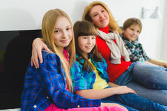 Mother hugging children sit on the bed indoor. happy family Stock Photos