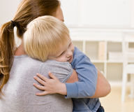 Mother hugging and comforting her son. Devoted mother hugging and comforting her son Stock Photography