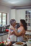 Mother hugging daughter in kitchen Royalty Free Stock Photography