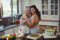 Mother hugging daughter in kitchen Royalty Free Stock Images