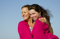 Mother hugging daughter in pink fabric Stock Photos