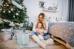 Mommy and daughter sitting by the christmas tree. Mother hugging daughter and sitting by the christmas tree Stock Photos