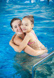 Mother hugging daughter in swimming pool Stock Image