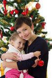 Mother hugging daughter under Christmas tree Royalty Free Stock Photo