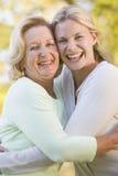 Mother hugging grown up daughter stock photos