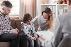 Mother hugging her autistic son, sitting next to his father duri. Ng family therapy royalty free stock photo