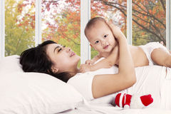 Mother hugging her baby on bed Royalty Free Stock Photos