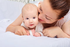 Mother hugging with her baby in the bedroom.Looking in the camer Royalty Free Stock Photography