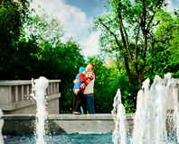 Mother hugging her child during walk in the park next to fountain. The concept of happiness and love. Boy 4-5 years old. Two persons Royalty Free Stock Photos