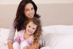 Mother hugging her daughter on the bed Royalty Free Stock Photo