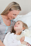 Mother hugging her daughter on the bed Stock Photo