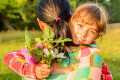 Mother hugging her daughter with flowers. Mother and daughter are showing affection and hugging Stock Image