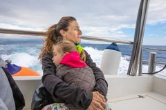Mother hugging her daughter in motorboat sailing in ocean. Mother hugging her daughter, four years old blonde girl with pigtail, sitting on the stern of royalty free stock photography