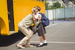 Mother hugging her daughter by school bus Royalty Free Stock Photos
