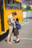 Mother hugging her daughter by school bus Stock Images