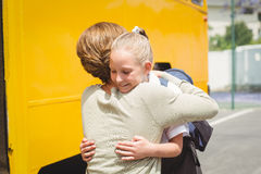 Mother hugging her daughter by school bus Royalty Free Stock Photo
