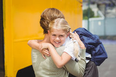 Mother hugging her daughter by school bus Stock Image