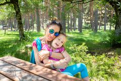 Mother hugging her daughter sitting on a picnic bench in a forest of the country stock image