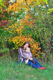 Mother hugging her son in autumn forest. Mom sits with the children of the forest and hugs him Royalty Free Stock Photography