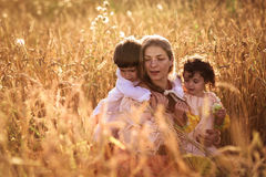 Mother hugging her son and daughter in a wheat field Stock Photo