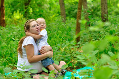 Mother hugging her son in forest. Mom sits with the children in the forest and hugs him Stock Photography