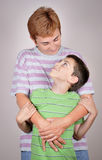 Mother hugging her son. Mother hugging her loving son. They are standing and looking at each other stock images