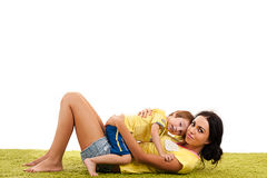 Mother hugging her son lying on the the green grass. Young mother hugging her son lying on the the green grass stock photo