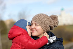 Mother hugging her son. At the park in autumn royalty free stock image