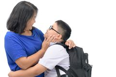 Mother hugging her son in uniform student. Before back to school isolated on white background, love concept Stock Images