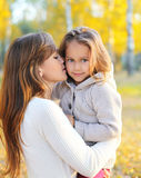 Mother hugging and kissing child in autumn Royalty Free Stock Photography