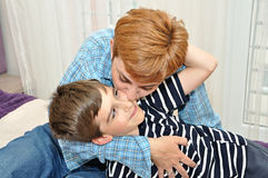 Mother hugging and kissing her son Stock Image