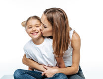 Mother hugging and kissing smiling daughter Stock Photo