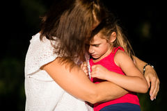 Mother hugging little daughter as she consoles her. Young worried girl kid being consoled by her mother Stock Images