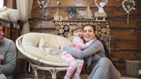 Mother hugging little daughter sitting by the fireplace with your family