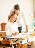 Mother hugging and praising daughter while doing homework Stock Photography