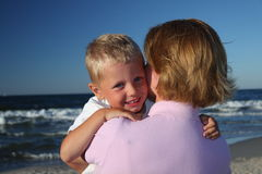 Mother hugging son on a beach Stock Photography