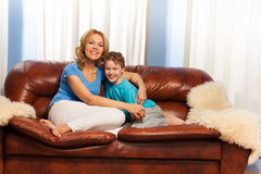 Mother hugs child sitting on couch at home Stock Photo