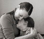 Mother hugs crying son. Mother comforts her crying/sobbing 6-year old son, low-key monochrome portrait Stock Image