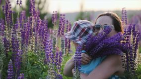 Mother hugs a cute little boy, a son in a blue t-shirt and patterned hat in a field, against a background of narrow. Mother in dark sunglasses hugs a cute little stock footage