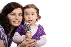 Mother hugs daughter, which sings into microphone Royalty Free Stock Images