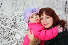 Mother hugs daughter in woods in snow Royalty Free Stock Image