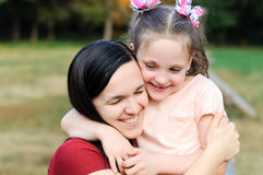 Mother hugs her daughter Stock Images