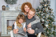 Mother hugs her husband and daughter near Christmas tree royalty free stock image