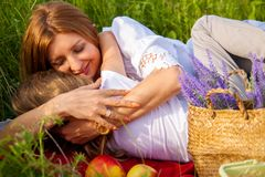 Beautiful young mother and her daughter in white having fun at the flower field in the summer. royalty free stock images