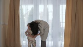 Mother hugs her little daughter but she`s breaking free from her hands. Young woman hugs her little daughter. Cute girl is capricious and don`t want to hugs with stock footage